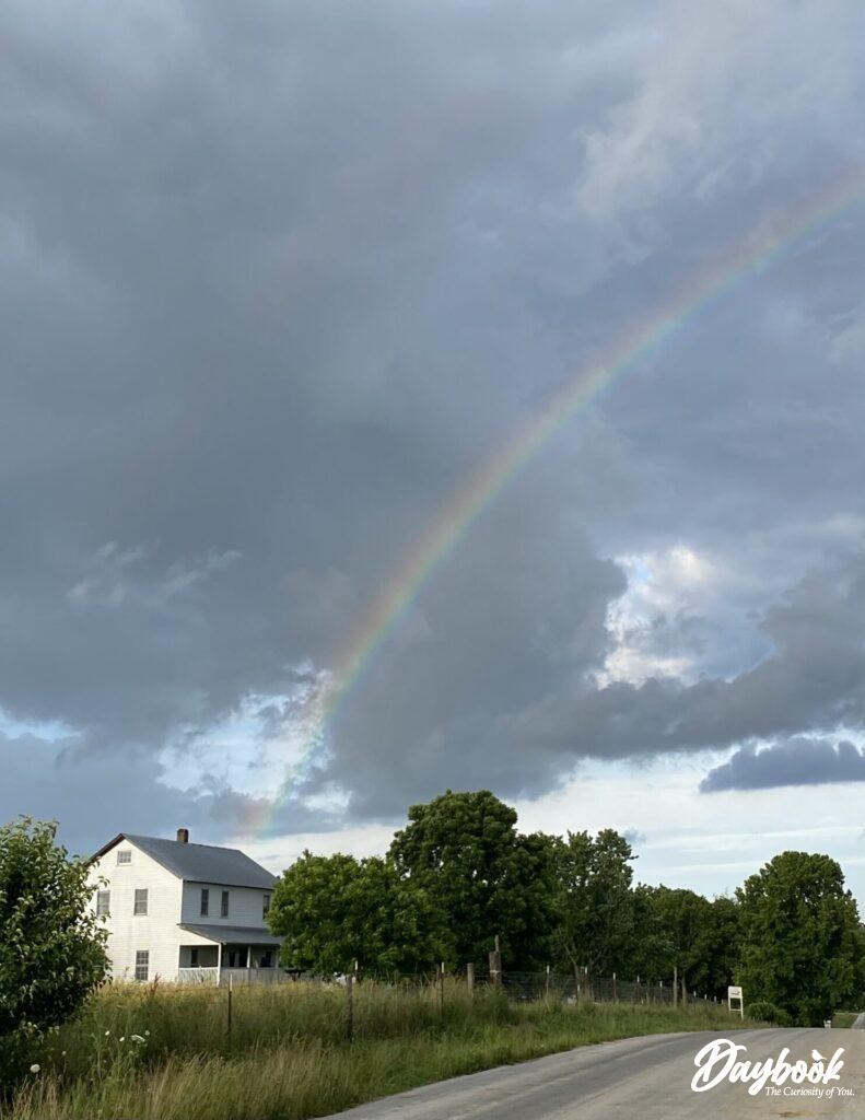 Amish house with rainbow in sky